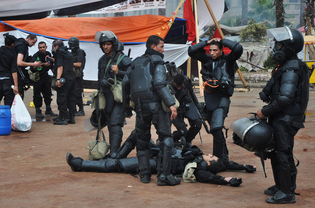. Egyptian security forces takes a break as they clear a sit-in camp set up by supporters of ousted Islamist President Mohammed Morsi near Cairo University in Cairo\'s Giza district, Egypt, Wednesday, Aug. 14, 2013. (AP Photo/Hussein Tallal)