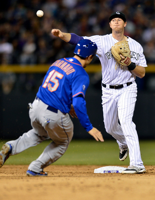 . Colorado Rockies second baseman DJ LeMahieu throws to first to complete the double play on New York Mets\' Ruben Tejada after forcing out Travis d\'Arnaud (15) at second during the sixth inning of a baseball game, Friday, May 2, 2014, in Denver. (AP Photo/Jack Dempsey)