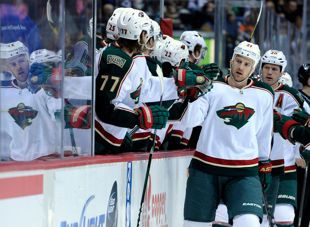 . Minnesota Wild center Kyle Brodziak (21) celebrates a goal with teammates on the bench during the first period of an NHL hockey game against the Colorado Avalanche on Saturday, March 16, 2013, in Denver. (AP Photo/Jack Dempsey)