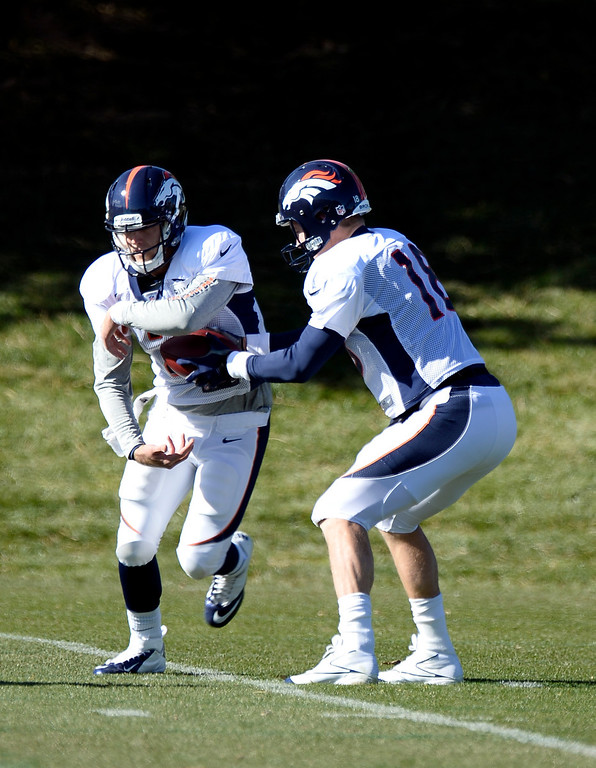 . Denver Broncos quarterback Peyton Manning (18) fakes the hand off to Denver Broncos quarterback Zac Dysert (2) during drills at practice November 6, 2013 at Dove Valley. (Photo by John Leyba/The Denver Post)
