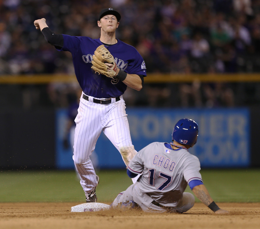 . Colorado Rockies second baseman DJ LeMahieu, left, forces out Texas Rangers\' Shin -Soo Choo at second base on the front end of a double play hit into by Josh Wilson to end the top of the eighth inning of the Rockies\' 8-2 victory in an interleague baseball game in Denver on Monday, May 5, 2014. (AP Photo/David Zalubowski)