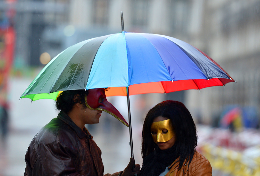 ". Revelers hold an umbrella at St Mark\'s square during the carnival on February 2, 2013 in Venice. The 2013 edition of the Venice carnival is untitled "" Live in Colour\"" and runs from January 26 to February 12.   VINCENZO PINTO/AFP/Getty Images"