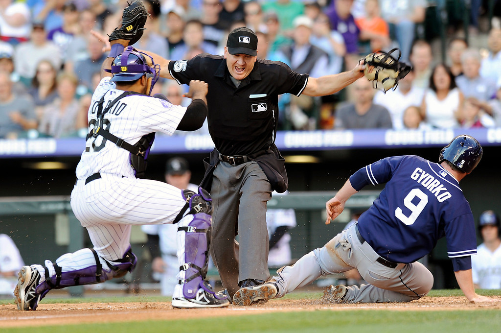 . San Diego Padres Jedd Gyorko, right, beats the tag by Colorado Rockies catcher Wilin Rosario, left, and is called safe by the umpire to score in the fourth inning of a baseball game on Thursday, June 6, 2013, in Denver. (AP Photo/Chris Schneider)