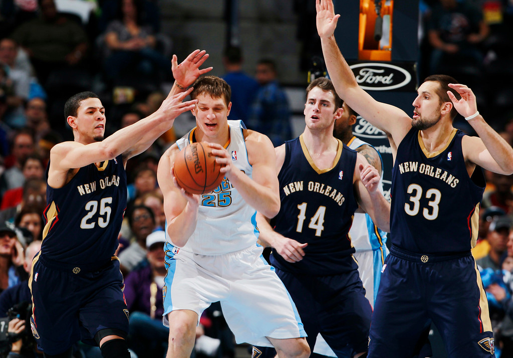 . Denver Nuggets center Timofey Mozgov, second from left, of Russia, pulls in a loose ball as, from left, New Orleans Pelicans guard Austin Rivers and forwards Jason Smith and Ryan Anderson cover in the third quarter of the Nuggets\' 102-93 victory in an NBA basketball game in Denver on Sunday, Dec. 15, 2013. (AP Photo/David Zalubowski)