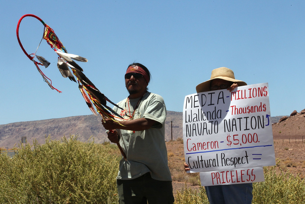 . Supai Waters, left, a Haeva Supai tribal member and and a woman who wished to be unidentified protest along highway, near Cameron, Ariz., on Sunday, June 23, 2013, to protest Florida aerialist Nik Wallenda\'s tightrope walk over the Little Colorado River Gorge. Wallenda plans to do the stunt without a safety harness. (AP Photo/Rick Bowmer)