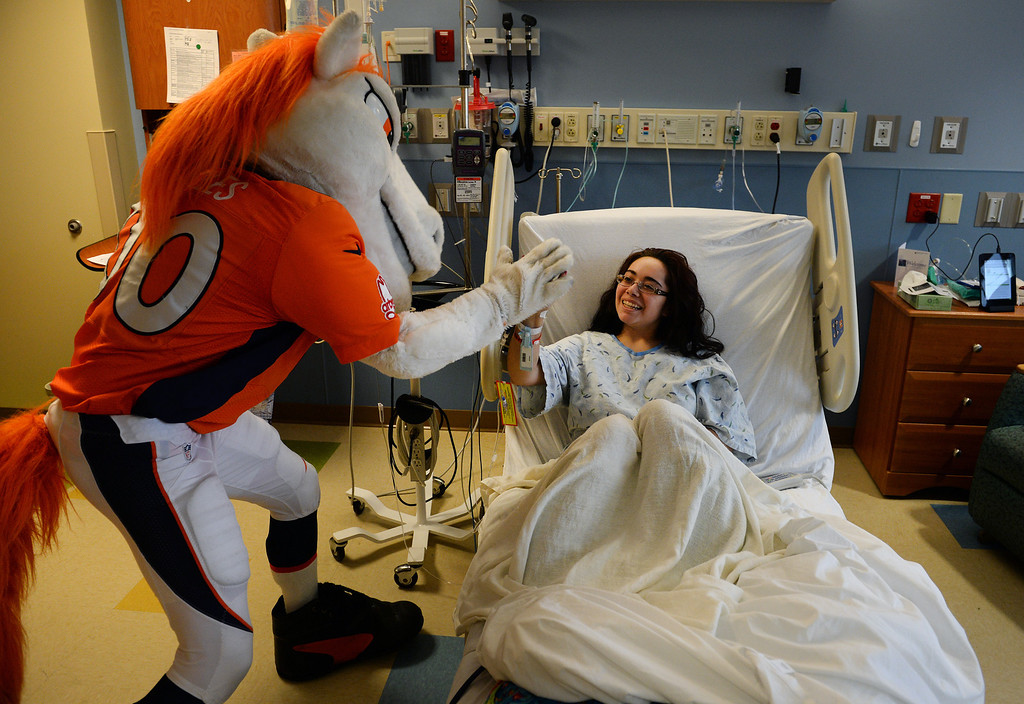 . Chereise Quintana, 17, gets a high five from Miles, the Broncos Mascot, as he made a surprise visit to her in her room in the Pediatric Intensive Care Unit at the  Rocky Mountain Hospital for Children in Denver, Co on January 14, 2014. Quintana recently had a tumor removed from her liver.   (Photo By Helen H. Richardson/ The Denver Post)