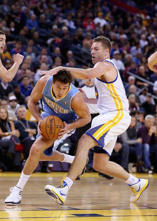 . OAKLAND, CA - NOVEMBER 29: Danilo Gallinari #8 of the Denver Nuggets is fouled by David Lee #10 of the Golden State Warriors at Oracle Arena on November 29, 2012 in Oakland, California. (Photo by Ezra Shaw/Getty Images)