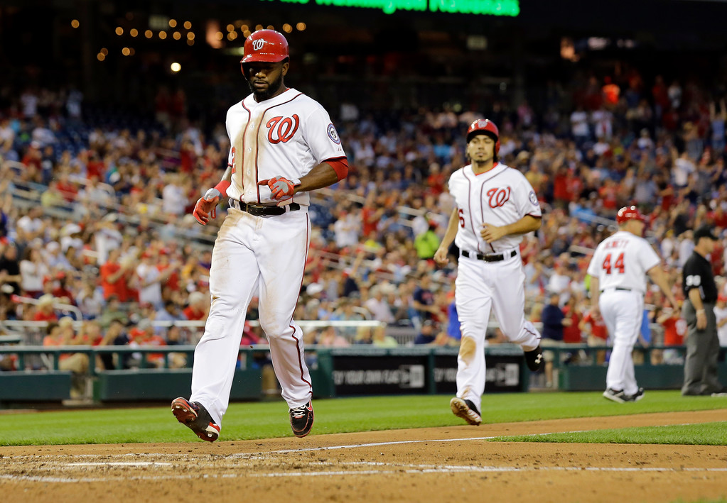 . Washington Nationals\' Denard Span and Anthony Rendon (6) score on Nationals\' Adam LaRoche\'s two-RBI triple during the fourth inning of a baseball game against the Colorado Rockies at Nationals Park, Thursday, June 20, 2013, in Washington. (AP Photo/Alex Brandon)