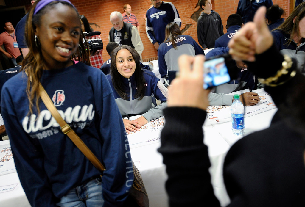 . Dionna Dorsey, left, poses for a photograph with Connecticut\'s Bria Hartley, seated at rear, during the autograph session at the men\'s and women\'s basketball teams\' First Night event Friday, Oct. 18, 2013, in Storrs, Conn. (AP Photo/Jessica Hill)