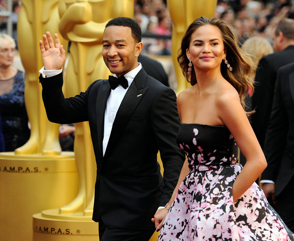 . John Legend, left, and Christine Teigen arrive at the Oscars on Sunday, March 2, 2014, at the Dolby Theatre in Los Angeles.  (Photo by Chris Pizzello/Invision/AP)