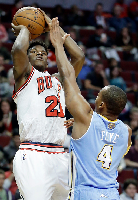 . Chicago Bulls guard Jimmy Butler (21) shoots over Denver Nuggets guard Randy Foye during the second half of an NBA preseason basketball game in Chicago on Friday, Oct. 25, 2013. The Bulls won 94-89. (AP Photo/Nam Y. Huh)