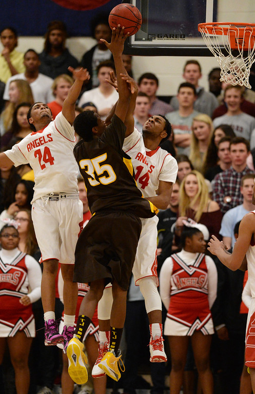 . DENVER, CO. JANUARY 24:Dominique Collier (24), left, and Stone Wright (14) of East High School defend against Jalen Rose of Thomas Jefferson High School (35) in the 1st half of the game at East High School in Denver, Colorado January 24, 2014. East High School won 91-62. (Photo by Hyoung Chang/The Denver Post)
