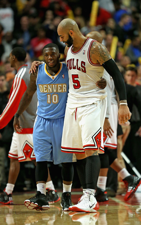 . Carlos Boozer #5 of the Chicago Bulls and Nate Robinson #10 of the Denver Nuggets hug after a preseason game at the United Center on October 25, 2013 in Chicago, Illinois. The Bulls defeated the Nuggets 94-89.  (Photo by Jonathan Daniel/Getty Images)