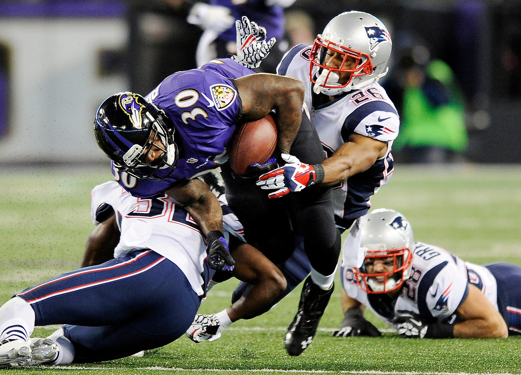 . Baltimore Ravens running back Bernard Pierce (30) is tackled by New England Patriots free safety Devin McCourty, left, and New England Patriots cornerback Logan Ryan in the first half of an NFL football game, Sunday, Dec. 22, 2013, in Baltimore. (AP Photo/Nick Wass)