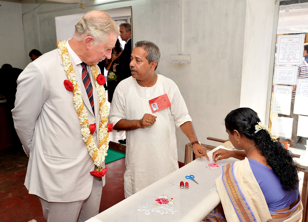 . Prince Charles, Prince of Wales studies a local woman working as an embroiderer during a visit to Jew Street in Jew Town on day 9 of an official visit to India on November 14, 2013 in Kochi, India.  (Photo by John Stillwell - Pool/Getty Images)