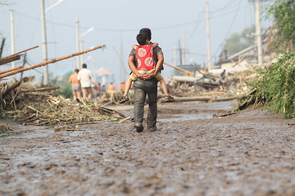 . A man walks with a child on his back after  heavy rain hits on August 18, 2013 in Fushun, China. 32 are missing and 15 are dead after a torrential rain hit Liaoning Province of China.  (Photo by ChinaFotoPress/ChinaFotoPress via Getty Images)