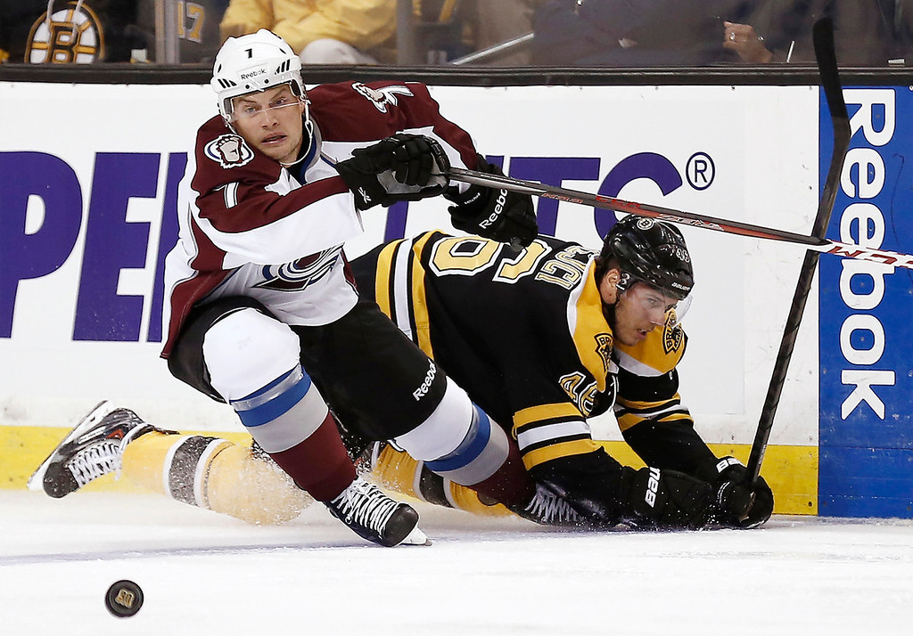 . Colorado Avalanche\'s John Mitchell (7) eyes a loose puck after knocking down Boston Bruins\' David Krejci during the first period of an NHL hockey game in Boston on Thursday, Oct. 10, 2013. (AP Photo/Winslow Townson)