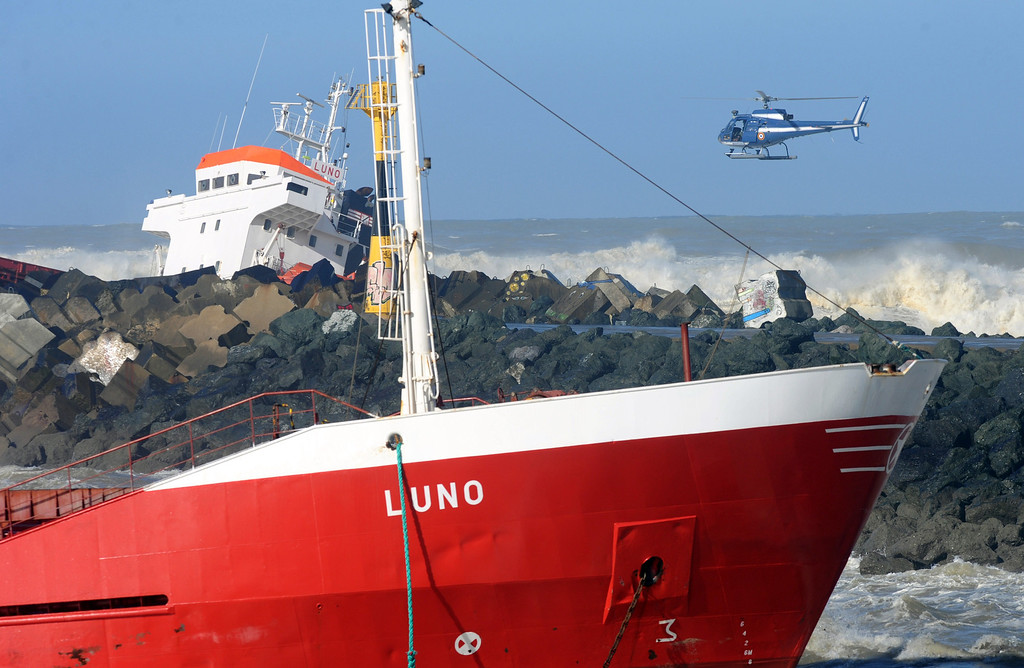 . An helicopter flies over  a Spanish cargo ship \'\'Luno\'\' which slammed into a dyke and split in two, injuring at least one sailor and raising concerns of a fuel leak, in Anglet, near the French port of Bayonne, on February 5, 2014.  AFP PHOTO/GAIZKA  IROZ/AFP/Getty Images