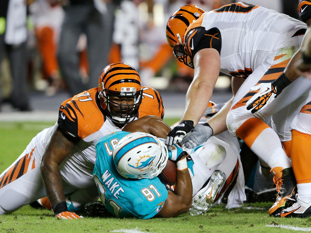 . Miami Dolphins defensive end Cameron Wake (91) recovers a fumble by Cincinnati Bengals quarterback Andy Dalton, between Bengals tackle Andre Smith (71) and guard Kevin Zeitler (68) during the first half of an NFL football game, Thursday, Oct. 31, 2013, in Miami Gardens, Fla. (AP Photo/Wilfredo Lee)