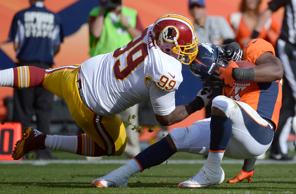 . Denver Broncos running back Knowshon Moreno (27) is tackled by Washington Redskins defensive end Jarvis Jenkins (99) during the first half.  (Photo by Tim Rasmussen/The Denver Post)