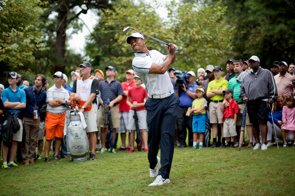 . Tiger Woods hits out of the rough on the 16th hole during the third round of play in the Tour Championship golf tournament at East Lake Golf Club, in Atlanta, Saturday, Sept. 21, 2013. (AP Photo/David Goldman)