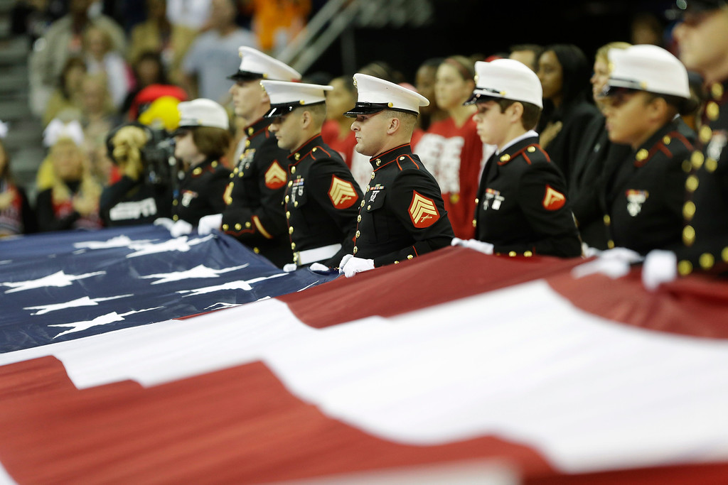 . A Marine honor guard carries the U.S. flag before the national championship game between Connecticut and Louisville at the women\'s Final Four of the NCAA college basketball tournament, Tuesday, April 9, 2013, in New Orleans. (AP Photo/Gerald Herbert)