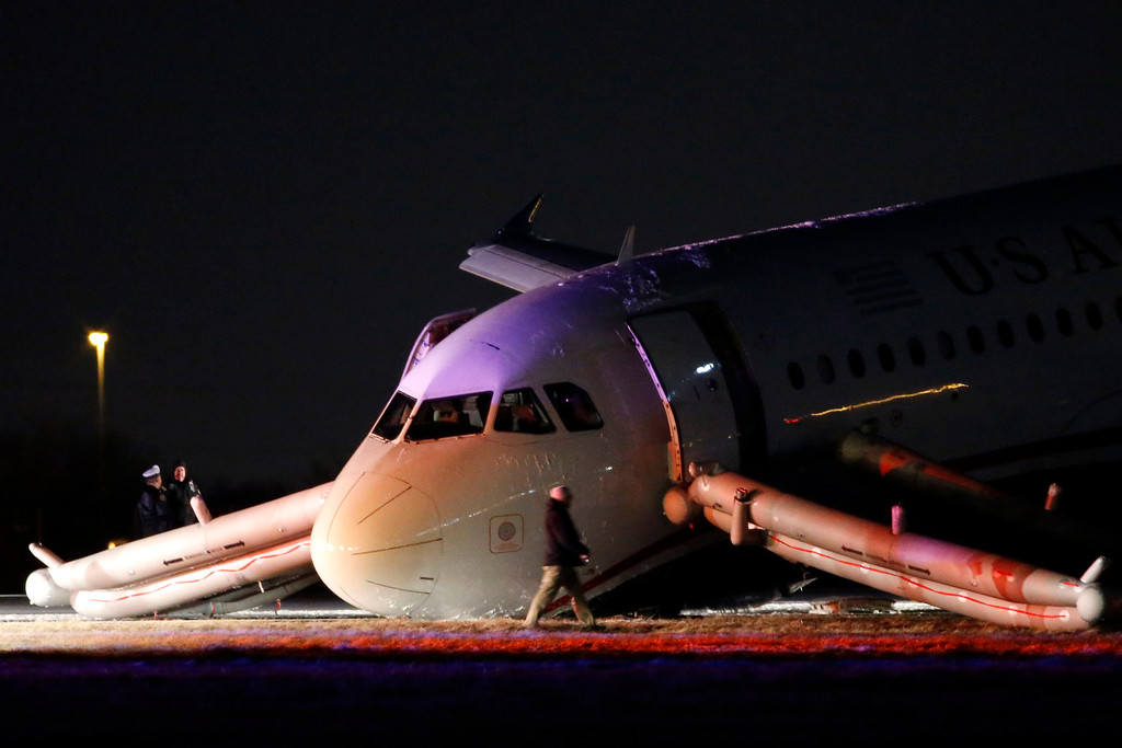 . An investigator walks near a damaged US Airways jet at the end of a runway at the Philadelphia International Airport, Thursday, March 13, 2014, in Philadelphia. Airline officials said the flight was heading to Fort Lauderdale, Fla., when the pilot was forced to abort takeoff around 6:30 p.m., after the front landing gear failed. An airport spokeswoman said no injuries have been reported. (AP Photo/Matt Slocum)