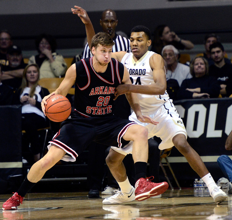. University of Colorado\'s George King (24) against Arkansas State\'s Kirk Van Slyke (20) during their game at the Coors Events Center on the CU Boulder Campus in Boulder, Colorado on November 18, 2013.  Photo by Paul Aiken / The Boulder Daily Camera.