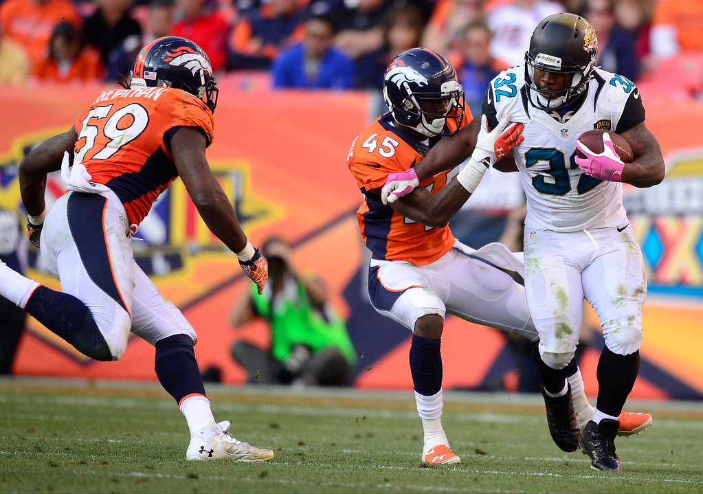 . Denver Broncos cornerback Dominique Rodgers-Cromartie (45) tries to tackle Jacksonville Jaguars running back Maurice Jones-Drew (32) in the fourth quarter.   (Photo by AAron Ontiveroz/The Denver Post)