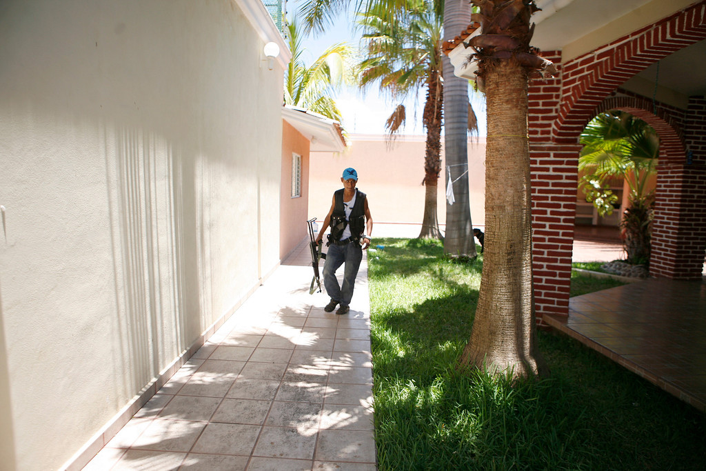 . A young man, who identifies himself as M3, walks inside the home of an alleged member of the Templar Knights cartel in the town of Aguililla, Mexico, July 25, 2013. The 18-year-old, who claims on a video posted on a national newspaper website, that he is a former Templar Knights gunman who deserted the cartel and joined the ranks of the Aguililla self-defense group because he was disgusted with the way the Templar Knights treat the community. (AP Photo/Gustavo Aguado)