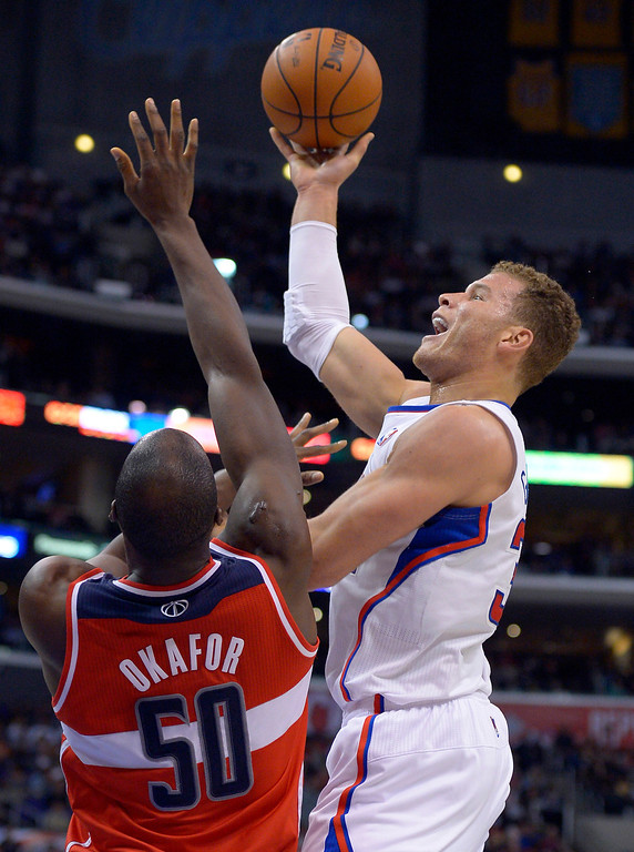 . Los Angeles Clippers forward Blake Griffin, right, puts up a shot against Washington Wizards center Emeka Okafor during the first half of their NBA basketball game, Saturday, Jan. 19, 2013, in Los Angeles. (AP Photo/Mark J. Terrill)