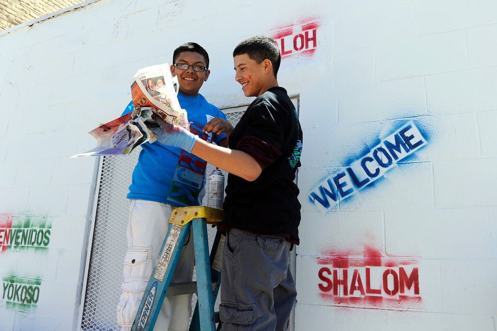 . DENVER, CO - MAY 3: Miguel Gallegos, 15, left, and Larry Nolasco, 14, join a group of their ninth-grade classmates from Bruce Randolph School to perform a day of service in the Five Points neighborhood by painting multicultural murals to celebrate the diverse cultures of the Five Points community. The ninth-grade class was divided in to groups and participated in various service jobs in four different locations in Denver during the day. (Photo By Kathryn Scott Osler/The Denver Post)