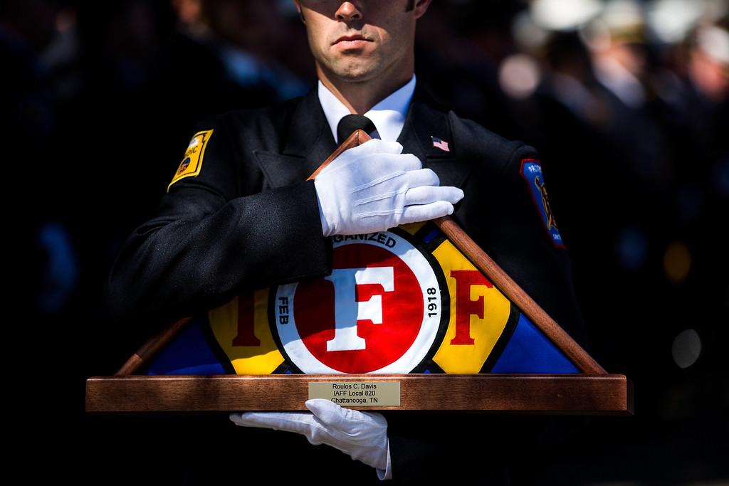 . A member of the IAFF Honor Guard carries a flag for a fallen firefighter during the annual IAFF Fallen Fire Fighter Memorial at Memorial Park in Colorado Springs, Colo., on Saturday, Sept. 21, 2013. (AP Photo/The Gazette, Kent Nishimura)