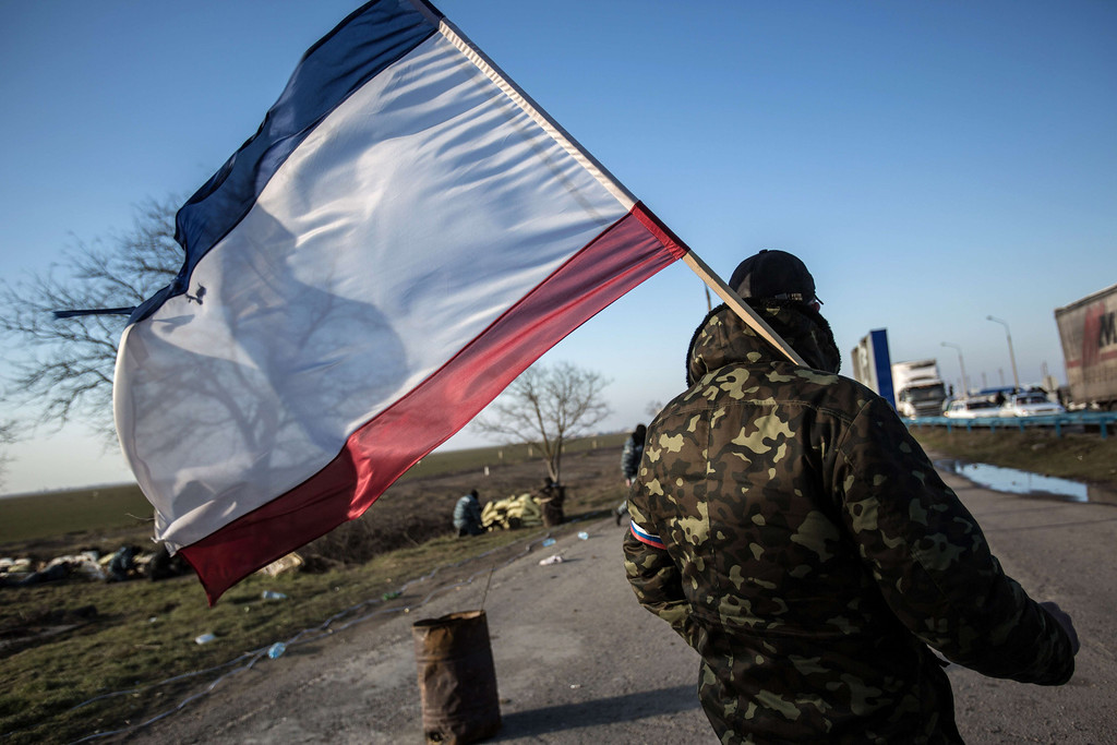 . A pro-Russia supporter waves a Crimean flag at Chongar checkpoint blocking the entrance to Crimea on March 10, 2014. Russia vowed on March 10 to unveil its own solution to the Ukrainian crisis that would run counter to US efforts and would appear to leave room for Crimea to switch over to Kremlin rule. The unexpected announcement came as Ukraine\'s new pro-European leaders raced to rally Western support in the face of the seizure by Kremlin-backed forces of the strategic Black Sea peninsula and plans to hold a Sunday referendum on switching Crimea\'s allegiance from Kiev to Moscow. ALISA BOROVIKOVA/AFP/Getty Images