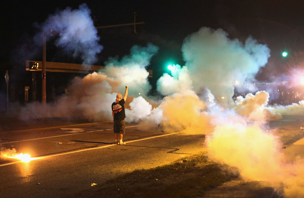 . A demonstrator, protesting the shooting death of teenager Michael Brown, stands his ground as police fire tear gas on August 13, 2014 in Ferguson, Missouri. (Photo by Scott Olson/Getty Images)