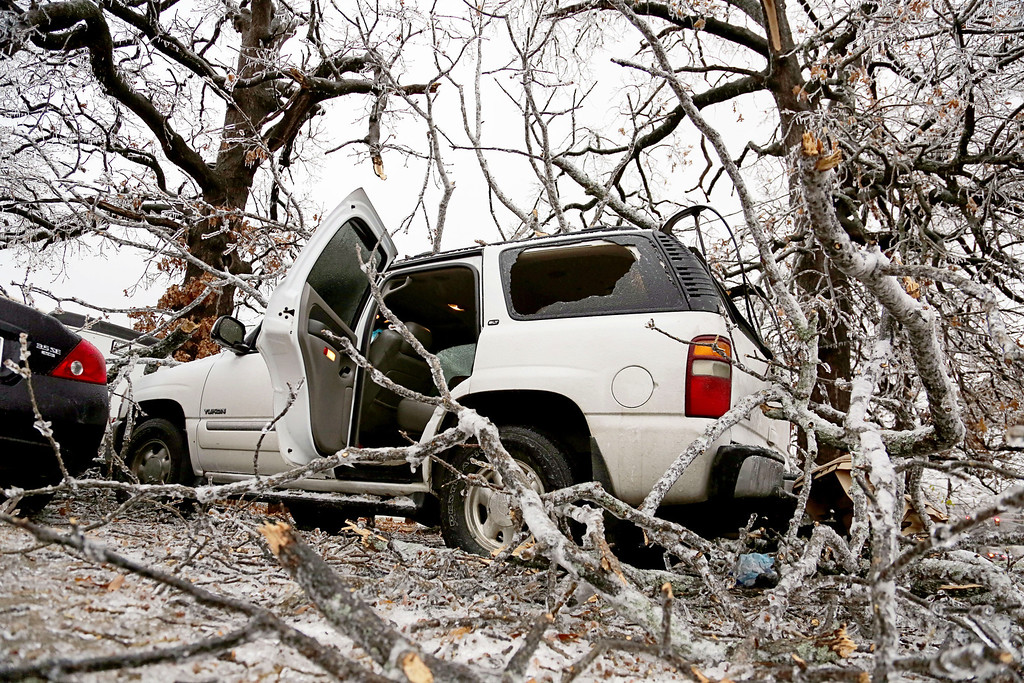 . An sports utility vehicle sits crushed in a driveway from ice-covered tree limbs in Paris, Texas, Friday, Dec. 6, 2013.  Winter storm and ice warnings are in effect through much of today for parts of six states in the Midwest, including Texas, Missouri, Illinois and Indiana. (AP Photo/The Paris News, Sam Craft)