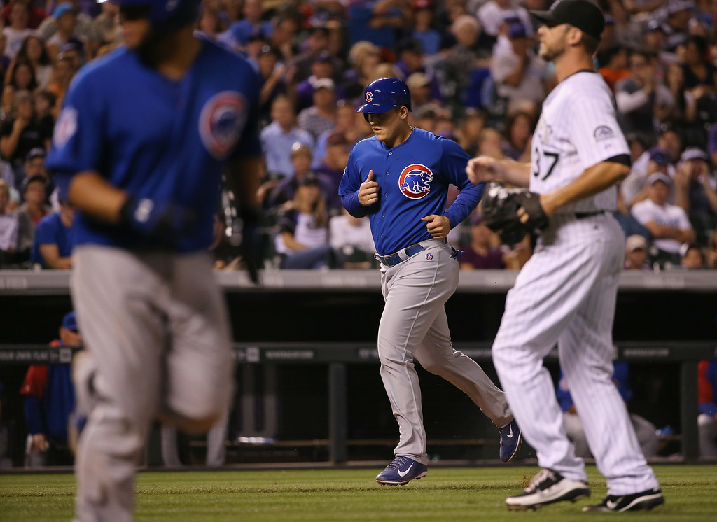 . DENVER, CO - AUGUST 05:  Anthony Rizzo #44 of the Chicago Cubs walks home to score as Nick Masset #37 of the Colorado Rockies gave up a bases loaded walk to Welington Castillo #5 of the Chicago Cubs as the Rockies held a 3-2 lead in the seventh inning at Coors Field on August 5, 2014 in Denver, Colorado.  (Photo by Doug Pensinger/Getty Images)