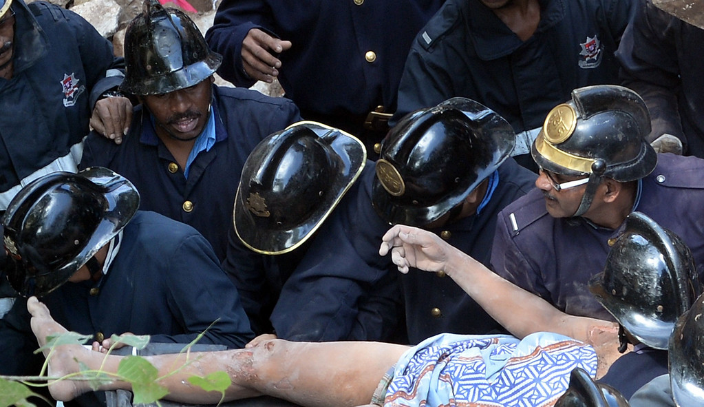 . Firefighters bring out a victim from the rubble at the site of a building collapse in Mumbai on September 27, 2013. AFP PHOTO/Indranil MUKHERJEE/AFP/Getty Images