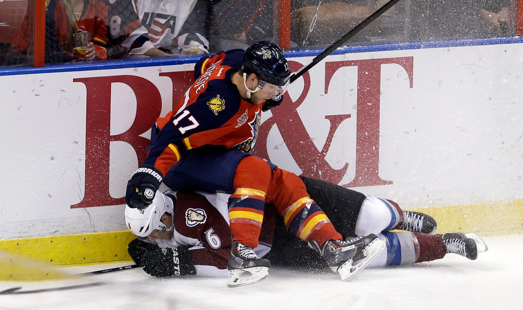. Florida Panthers center Jesse Winchester (17) Colorado Avalanche defenseman Erik Johnson (6) crash into the boards during the third period of an NHL hockey game in Sunrise, Fla., Friday, Jan. 24, 2014. The Avalanche won 3-2. (AP Photo/Alan Diaz)