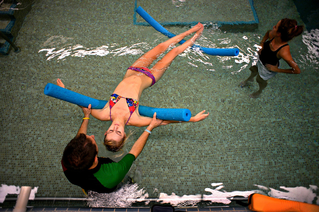 . Karen Gorden said her daughter loved the pool workouts because of the freedom, and the chance to more closely approximate walking. �Gravity is not working against her,� Karen said. Exercise specialist TC Doyle worked with Mackenzie on loosening her hips and arching to strengthen abdominal muscles. (Photo By Craig F. Walker / The Denver Post)