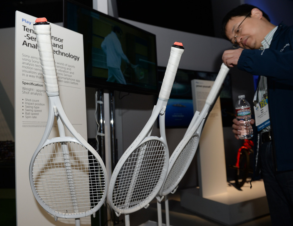 . An attendee examines a Sony bluetooth tennis racket on the final day of the 2014 International Consumer Electronics Show (CES) on January 10, 2014 in Las Vegas. The prototype racket is equipped with vibration and motion sensors  which collect information about the player\'s swing speed, ball speed and spin rate and relay it to a Smartphone or tablet. (Robyn Beck/AFP/Getty Images)