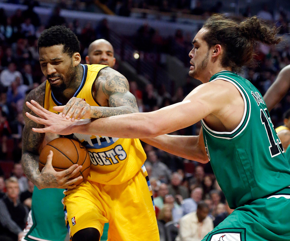 . Denver Nuggets guard Wilson Chandler, left, battles Chicago Bulls center Joakim Noah for a rebound during overtime of an NBA basketball game, Monday, March 18, 2013, in Chicago. The Nuggets won 119-118. (AP Photo/Charles Rex Arbogast)