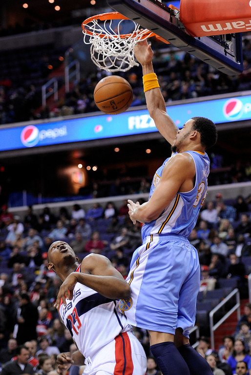 . Denver Nuggets center JaVale McGee, right, dunks over Washington Wizards forward Kevin Seraphin (13) during the first half of an NBA basketball game, Friday, Feb. 22, 2013, in Washington. (AP Photo/Nick Wass)