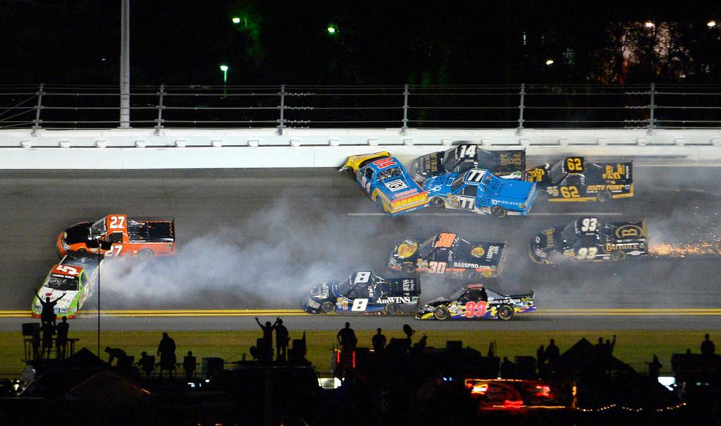 . A wreck between Turns 3 and 4 ensnares Tim George Jr. (5), Jeff Agnew (27), Chris Fontaine (84), Brennan Newberry (14), German Quiroga (77), Brendan Gaughan (62), Jason White (93), Ryan Truex (30), Bryan Silas (99) and Max Gresham (8) during the NASCAR Truck Series auto race at Daytona International Speedway in Daytona Beach, Fla., Friday, Feb. 22, 2013. (AP Photo/Phelan M. Ebenhack)