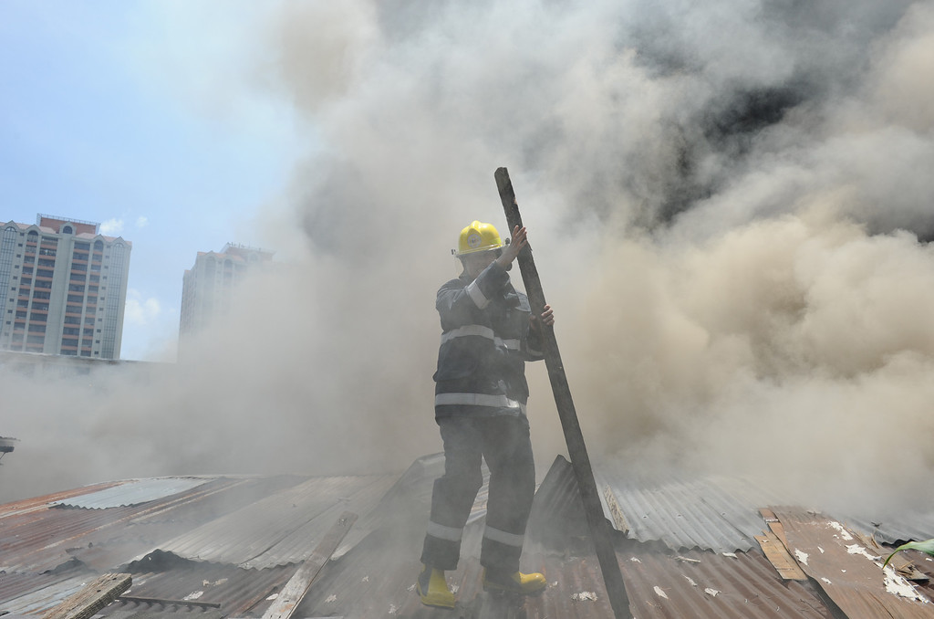 . A fireman removes part of a roof as he to tries to extinguish burning houses as a fire engulfs a shanty town at the financial district of Manila on July 11, 2013, leaving more than 1,000 people homeless according to city officials.  There were no immediate reports of casualties from the blaze, which occurred mid-morning amid government plans to relocate thousands of families living in areas vulnerable to floods and typhoons. TED ALJIBE/AFP/Getty Images