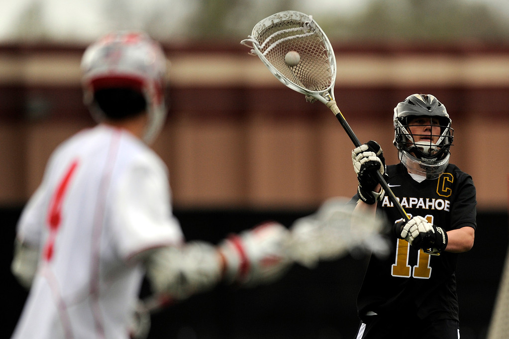 . DENVER, CO - MAY 15: Arapahoe senior goalie Ryan Smith #11 looks to pass against Regis Jesuit junior defenseman Connor Moran #4 during a CHSAA 5A boys lacrosse semifinal game on May 15, 2013, in Denver, Colorado. Arapahoe won 13-5 to advance to the finals. (Photo by Daniel Petty/The Denver Post)