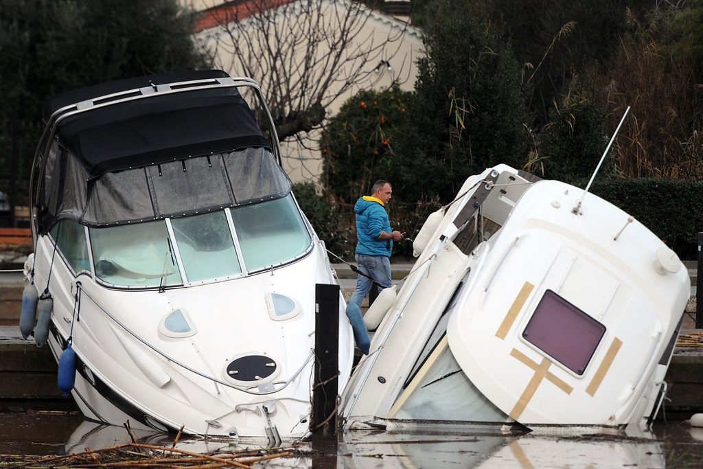 """. A man looks at damaged boats in the harbour of La Londe-les-Maures, southeastern France on Januray 20, 2014. River levels were receding early today in southeastern France after \""""historic\"""" floods left two people dead and more than 150 were airlifted to safety. A third man disappeared while out on his boat and 4,000 homes have been left without power after the deluge in the department of Var, they said. Local official Laurent Cayrel said one of the victims, a 73-year-old man, died in his basement, while the other was swept away in his car.   BORIS HORVAT/AFP/Getty Images"""