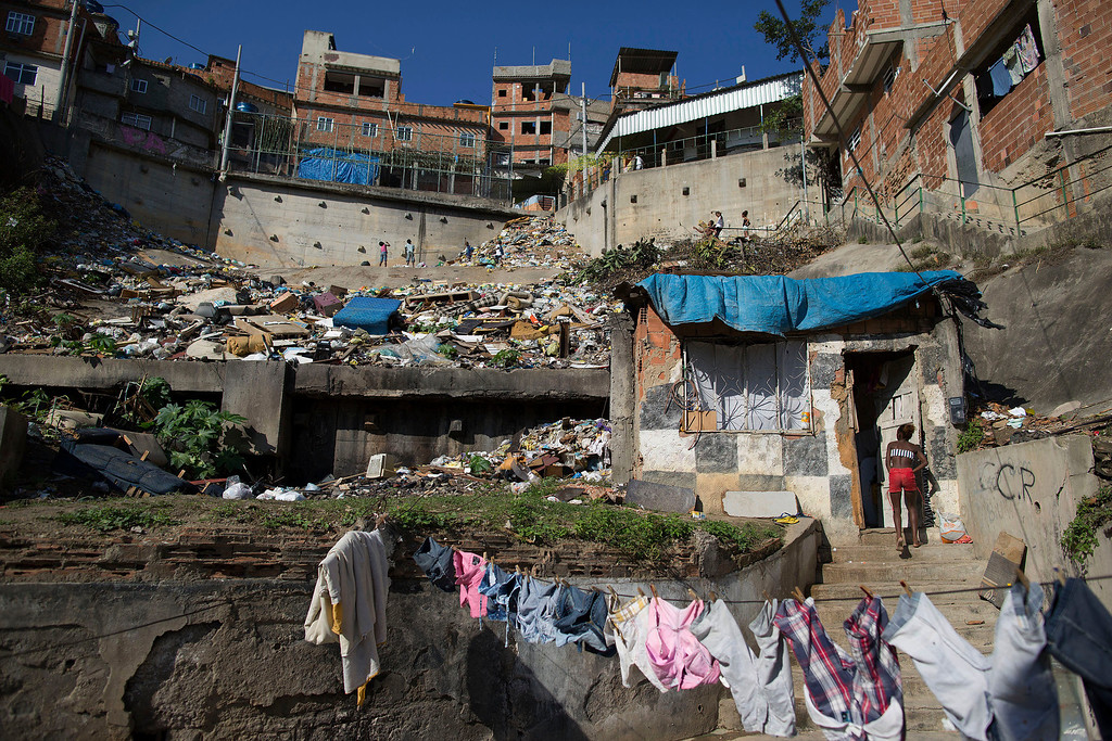 . In this Monday, June 2, 2014, a woman enters her shack on a hillside next to a landfill in the Mangueira slum in Rio de Janeiro, Brazil. Less than half a kilometer separates the sprawling slum from the Maracana stadium, where seven World Cup matches will be played, including the July 13 final. (AP Photo/Leo Correa)