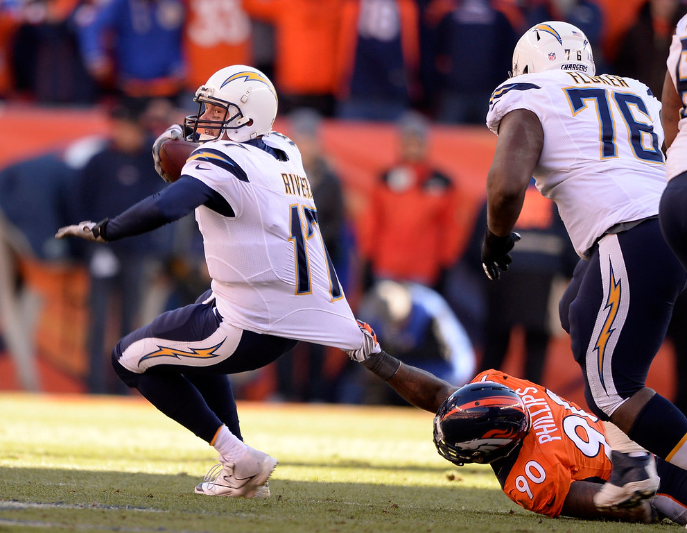 . Denver Broncos defensive end Shaun Phillips (90) pulls down San Diego Chargers quarterback Philip Rivers (17) for a first quarter sack. The Denver Broncos vs. The San Diego Chargers in an AFC Divisional Playoff game at Sports Authority Field at Mile High in Denver on January 12, 2014. (Photo by John Leyba/The Denver Post)