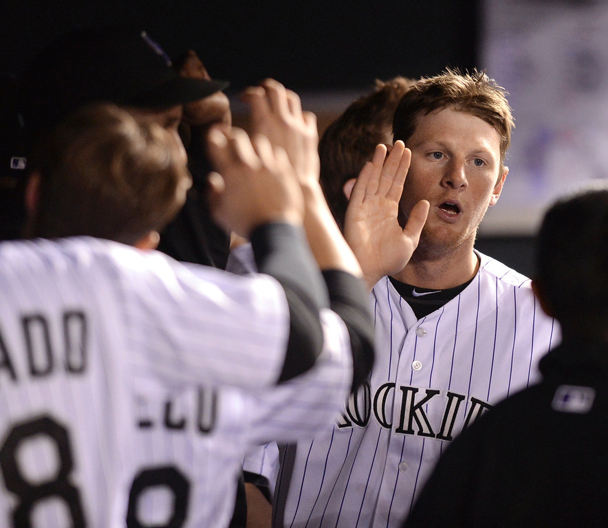 . DENVER, CO - MAY 15: Colorado\'s DJ LeMahieu accepted congratulations teammates in the dugout after scoring a run in the seventh inning.The Colorado Rockies hosted the San Diego Padres at Coors Field  Friday night, May 16, 2014. (Photo by Karl Gehring/The Denver Post)
